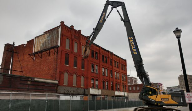 High Reach excavator performing demolition on building