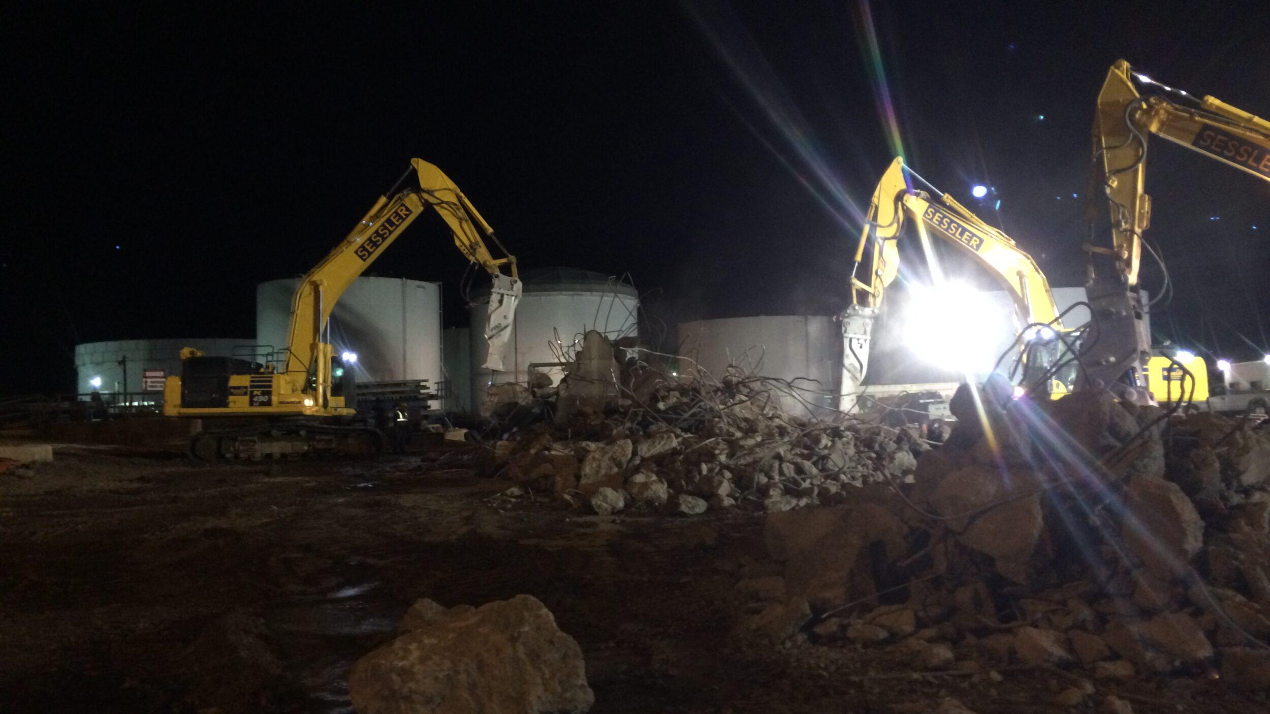 two excavators removing concrete