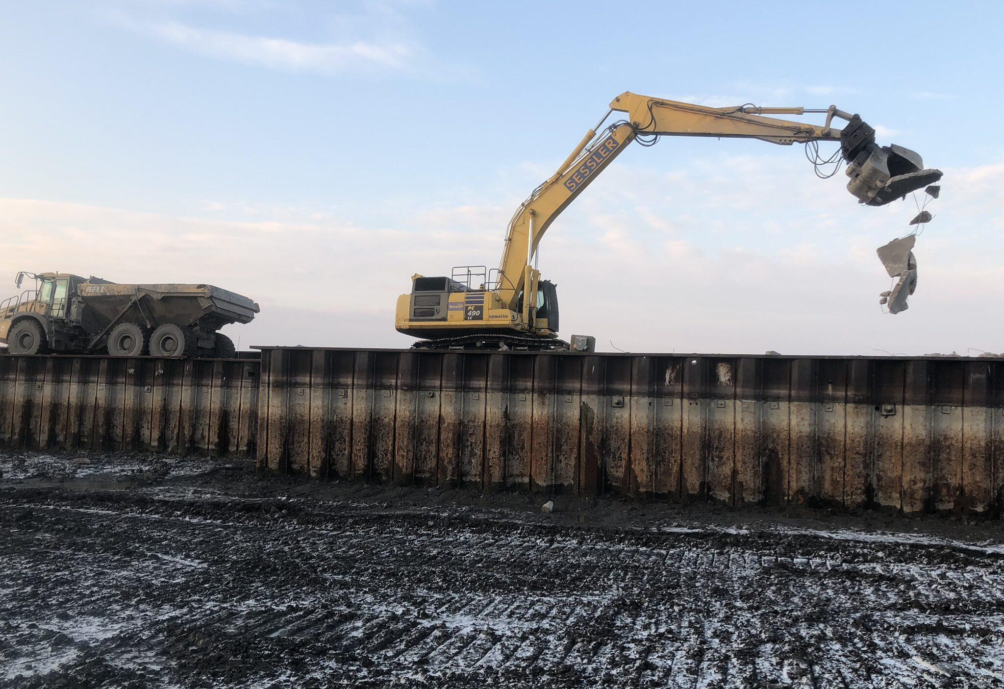 Excavator on marina wall