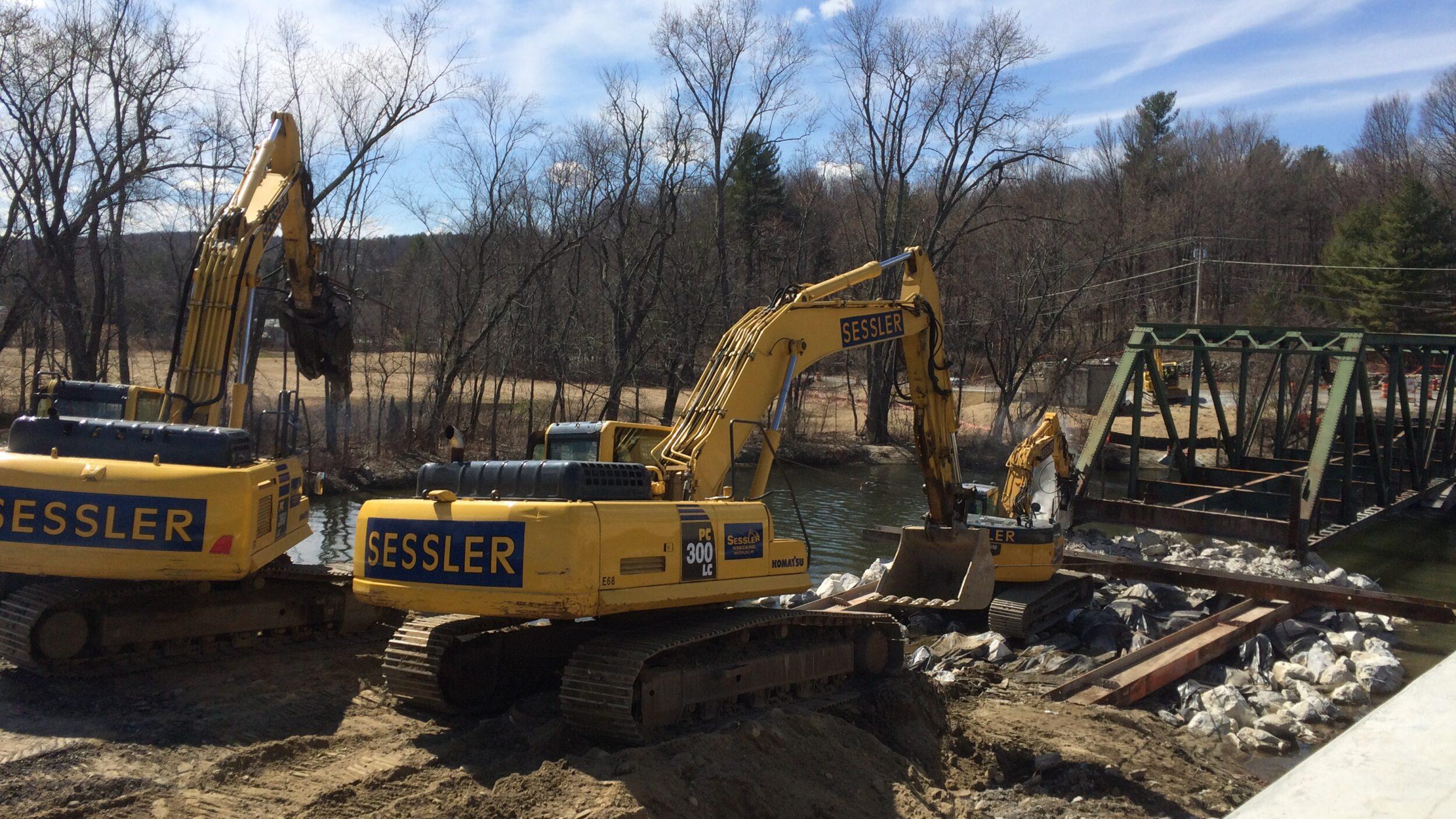 Excavators pulling bridge on barge