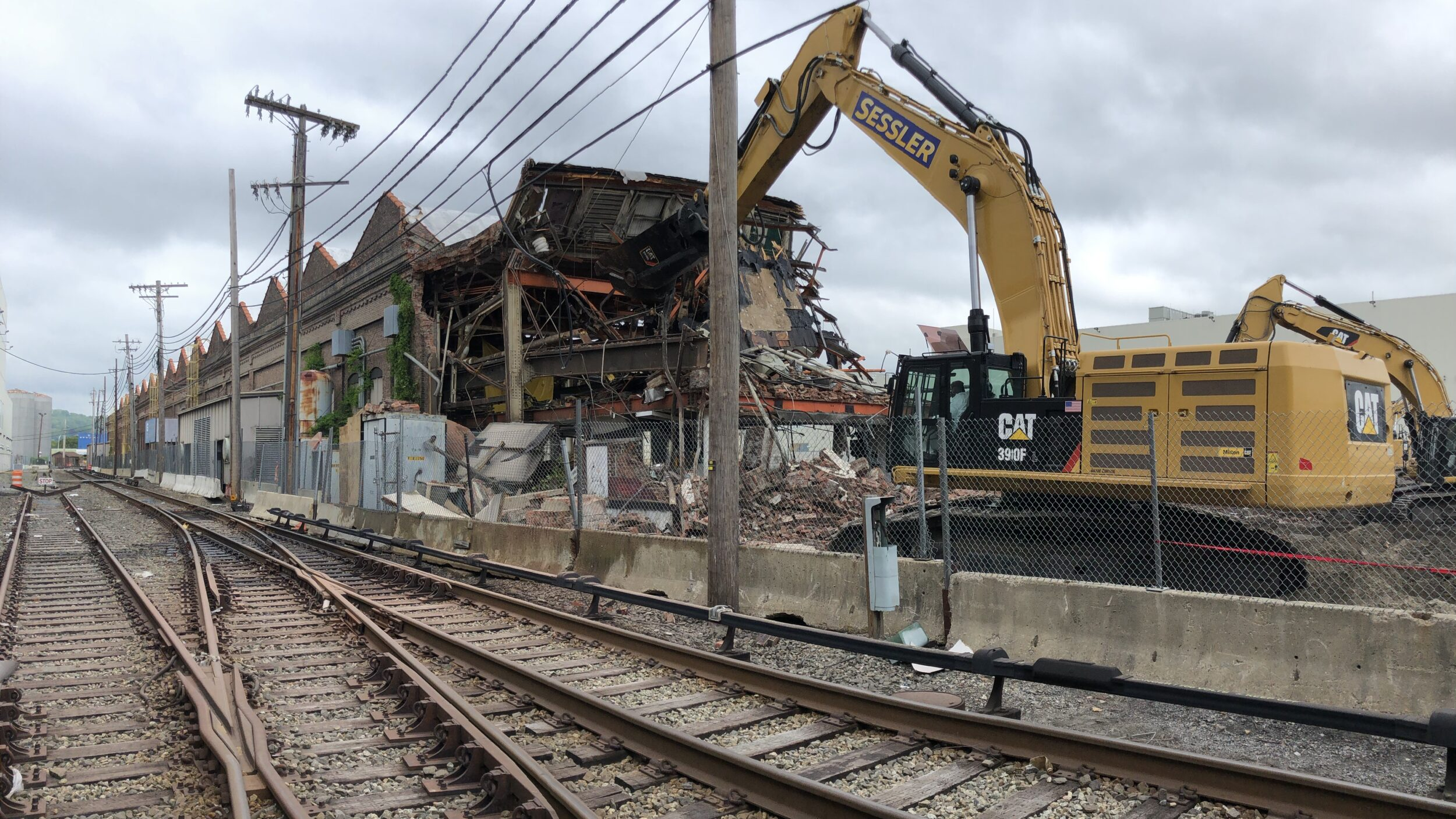 Excavator demoing building along railroad