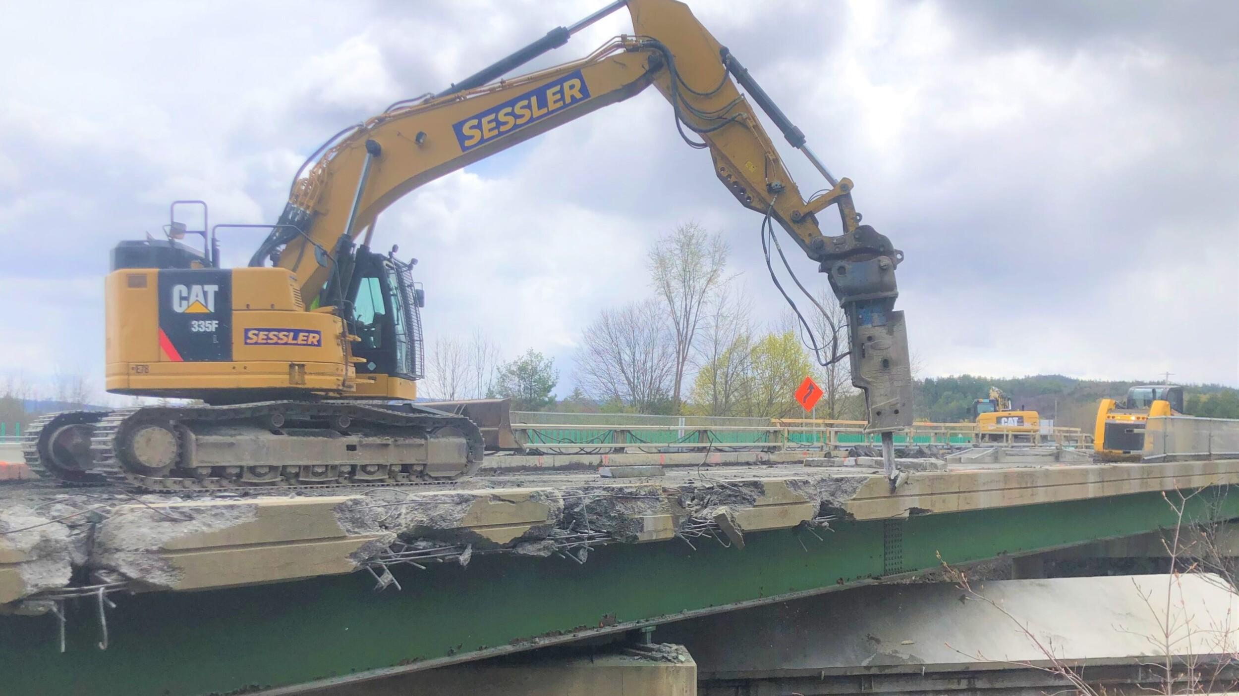 Excavator Hammering concrete on bridge